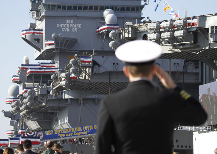 A Navy officer salutes during the inactivation ceremony for the first nuclear powered aircraft carrier USS Enterprise at Naval Station Norfolk Saturday, Dec. 1, 2012 in Norfolk, Va. The ship served in the fleet for 51 years. (AP Photo/Steve Helber)