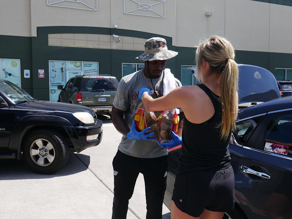 Detroit Lions running back Adrian Peterson helps out at a food distribution event in Houston last June. as part of his charitable giving to help alleviate food insecurity in communities around the country. He will be donating 100,000 meals to help combat hunger in Detroit this holiday season.