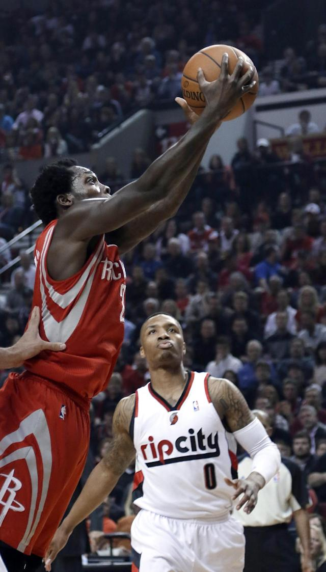 Houston Rockets guard Patrick Beverley, left, goes to the basket asPortland Trail Blazers guard Damian Lillard watches during the first half of Game 3 of an NBA basketball first-round playoff series in Portland, Ore., Friday, April 25, 2014. (AP Photo/Don Ryan)