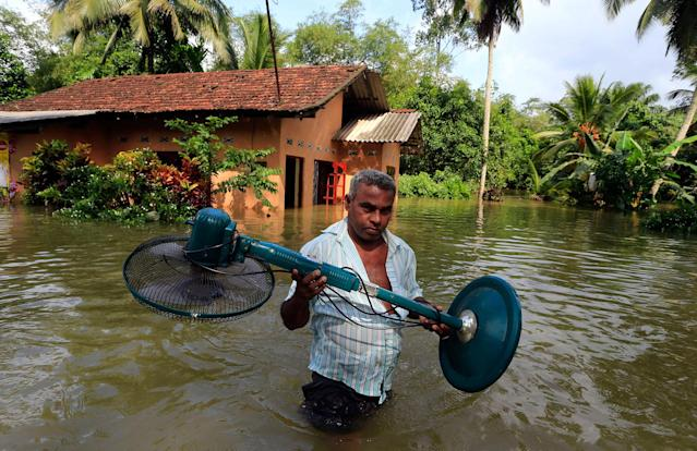 <p>A Sri Lankan man removes belongings from his submerged house at Wehangalla village in Kalutara district, Sri Lanka, Saturday, May 27, 2017. (AP Photo/Eranga Jayawardena) </p>