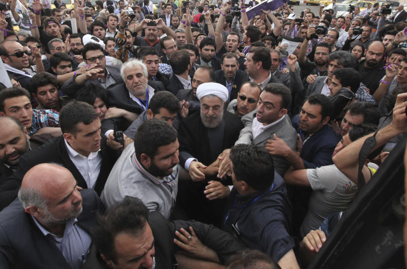 Iranian Presidential candidate Hasan Rowhani, center, a former Iran's nuclear negotiator, leaves at the conclusion of his campaign rally at the northwestern city of Tabriz, Iran, Monday, June 10, 2013. He talks about easing the political restrictions imposed by Iranian authorities. He told crowds that rebuilding ties with Western governments is better than denouncing them as irreconcilable enemies. At a rally Monday, crowds gathered for candidate Hasan Rowhani broke out in chants for the release of political prisoners. (AP Photo/Vahid Salemi)