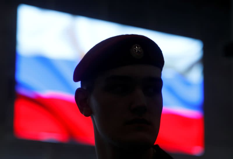 A serviceman stands in front of a screen displaying a Russian flag during a news briefing near Moscow