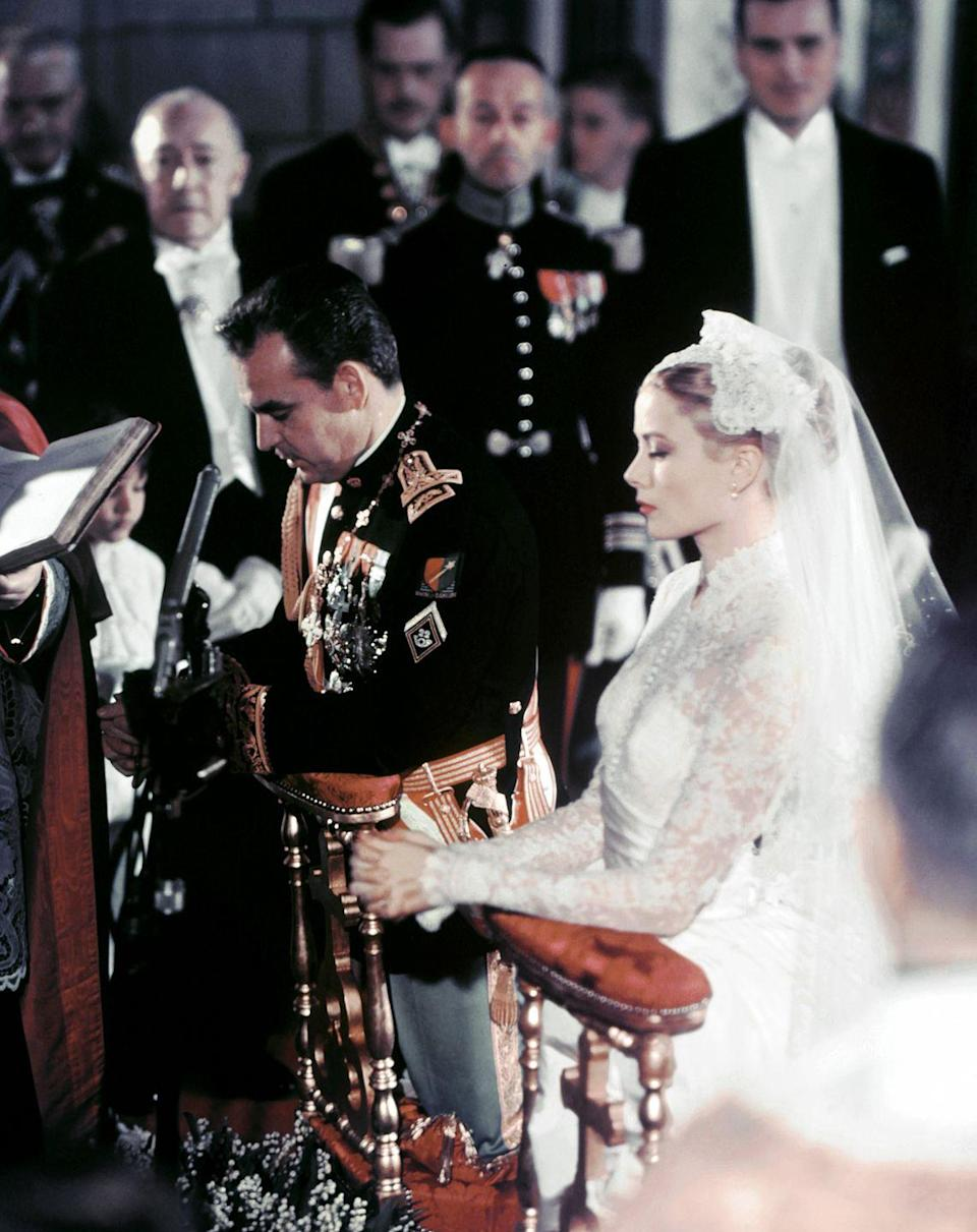 """<p>Princess Grace and Prince Rainier III of Monaco share a quiet moment as they kneel at the altar during their religious wedding ceremony in Monaco's Cathedral of St. Nicholas. The couple was <a href=""""https://www.townandcountrymag.com/society/tradition/a33446283/olivia-de-havilland-grace-kelly-prince-rainier-monaco-introduction/"""" rel=""""nofollow noopener"""" target=""""_blank"""" data-ylk=""""slk:also joined"""" class=""""link rapid-noclick-resp"""">also joined</a> during a traditional civil ceremony the day before.</p>"""