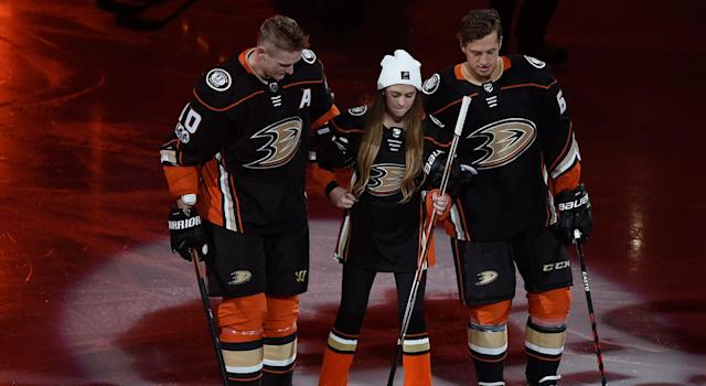 "<a class=""link rapid-noclick-resp"" href=""/nhl/teams/ana/"" data-ylk=""slk:Anaheim Ducks"">Anaheim Ducks</a> right wing <a class=""link rapid-noclick-resp"" href=""/nhl/players/3365/"" data-ylk=""slk:Corey Perry"">Corey Perry</a>, left, and center <a class=""link rapid-noclick-resp"" href=""/nhl/players/5391/"" data-ylk=""slk:Rickard Rakell"">Rickard Rakell</a>, right, assist Katie Hawley as she is introduced as the ""21st Duck"" during opening night. (AP Photo/Kelvin Kuo)"