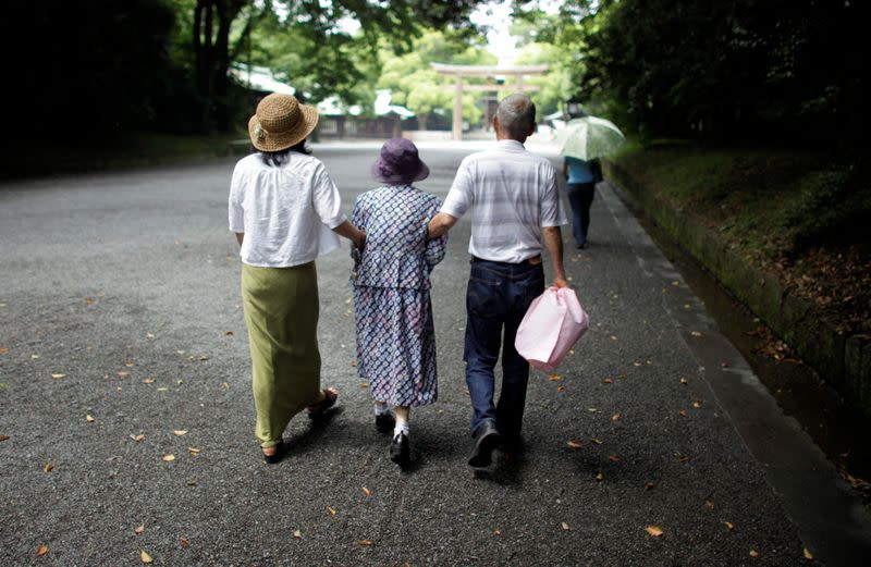 FILE PHOTO: An elderly woman is led to a temple in Tokyo in this July 17, 2009 file photo