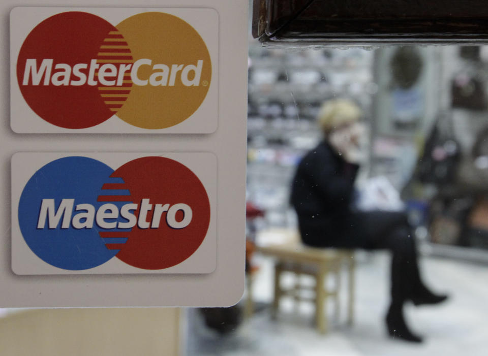 A sign with a logo of MasterCard is seen on the door of a shoe shop. Photo: Eduard Korniyenko/Reuters