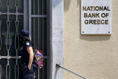 A coast guard officer looks through a locked gate at a National Bank of Greece branch in Piraeus port near Athens, Greece June 30, 2015. REUTERS/Yannis Behrakis