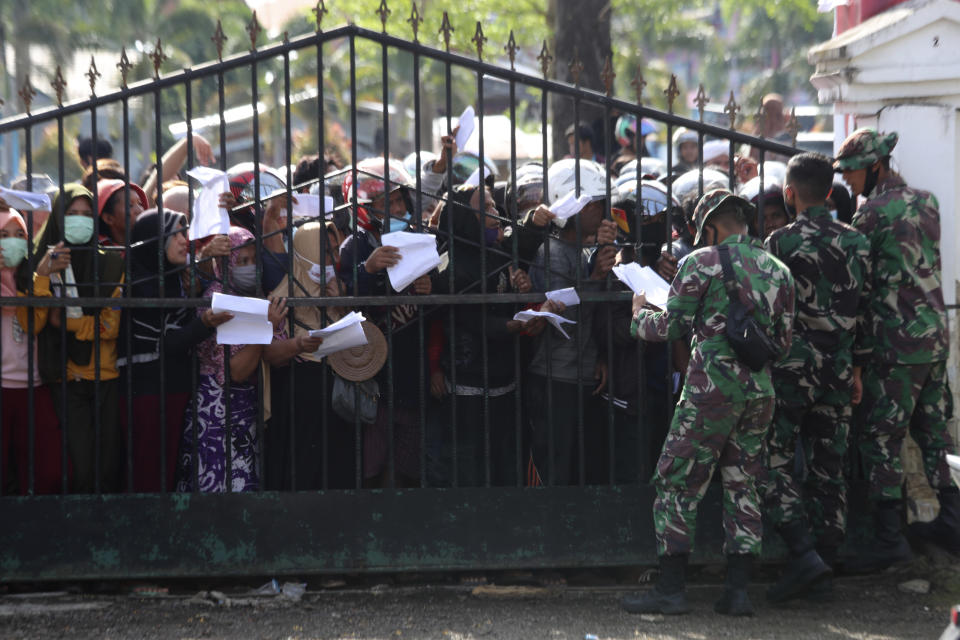People affected by earthquake queue up for relief goods in Mamuju, West Sulawesi, Indonesia, Monday, Jan. 18, 2021. Aid was reaching the thousands of people left homeless and struggling after an earthquake that killed a number of people in the province where rescuers intensified their work Monday to find those buried in the rubble. (AP Photo/Joshua Marunduh)