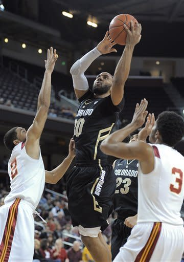 Colorado guard Carlon Brown, center, puts up a shot as Southern California guards Greg Allen, left, and Alexis Moore defend during the first half of an NCAA college basketball game Thursday, Jan. 26, 2012, in Los Angeles. (AP Photo/Mark J. Terrill)