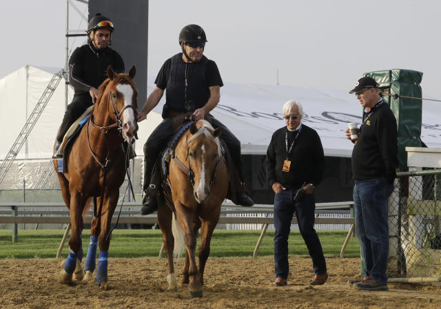 Improbable, left, is lead back to the barn as trainer Bob Baffert, second from right, and co-owner, Elliott Walden, walk along during training for Saturday's Preakness horse race at Pimlico race track in Baltimore, Friday, May 17, 2019. (AP Photo/Steve Helber)