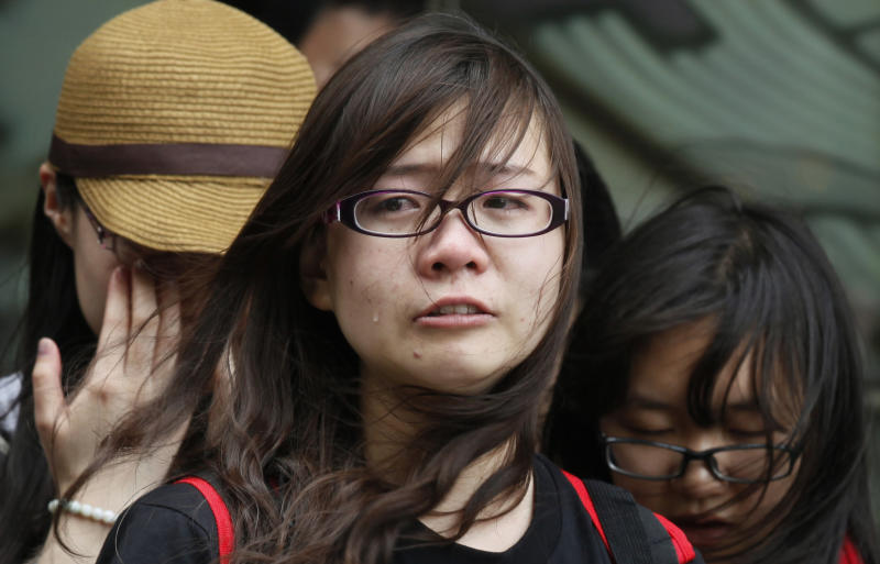 A tearful fan along with others sings a song of the late Hong Kong actor-singer Leslie Cheung outside a hotel where Cheung jumped to his death, in Hong Kong Monday, April 1, 2013. Cheung's fans placed flowers to mark the 10th anniversary of the death of Hong Kong screen and singing legend Cheung. (AP Photo/Kin Cheung)