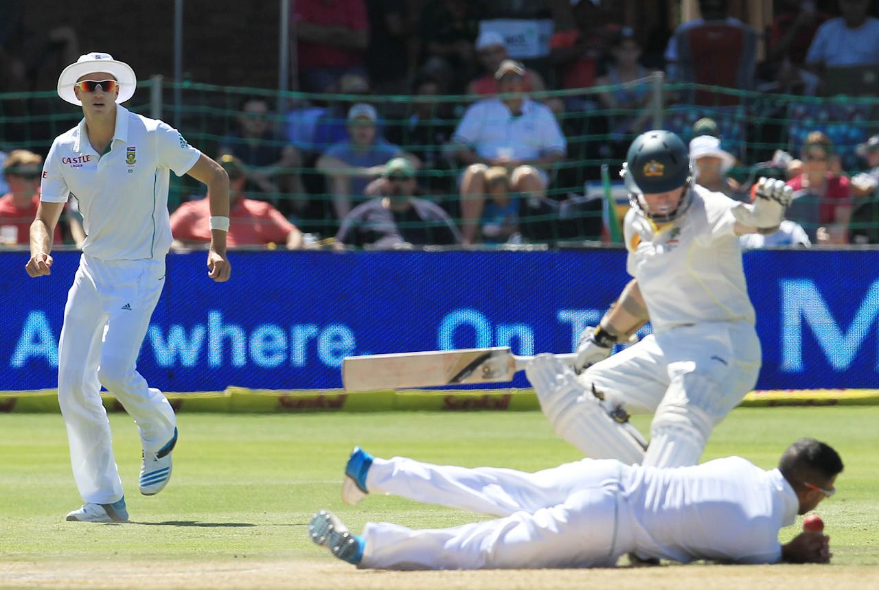 South Africa's bowler Morne Morkel, left, watches as JP Duminy, bottom, attempts fielding his own bowling as Australia's batsman Chris Rogers, right, avoids colliding with him on the fourth day of their 2nd cricket test match at St George's Park in Port Elizabeth, South Africa, Sunday, Feb. 23, 2014. (AP Photo/ Themba Hadebe)