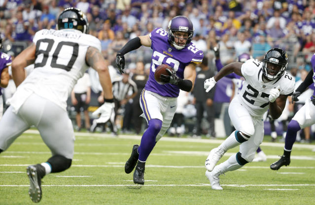 Minnesota Vikings defensive back Harrison Smith (22) runs up field between Jacksonville Jaguars' James O'Shaughnessy, left, and Leonard Fournette, right, after intercepting a pass during the first half of an NFL preseason football game, Saturday, Aug. 18, 2018, in Minneapolis. (AP Photo/Bruce Kluckhohn)