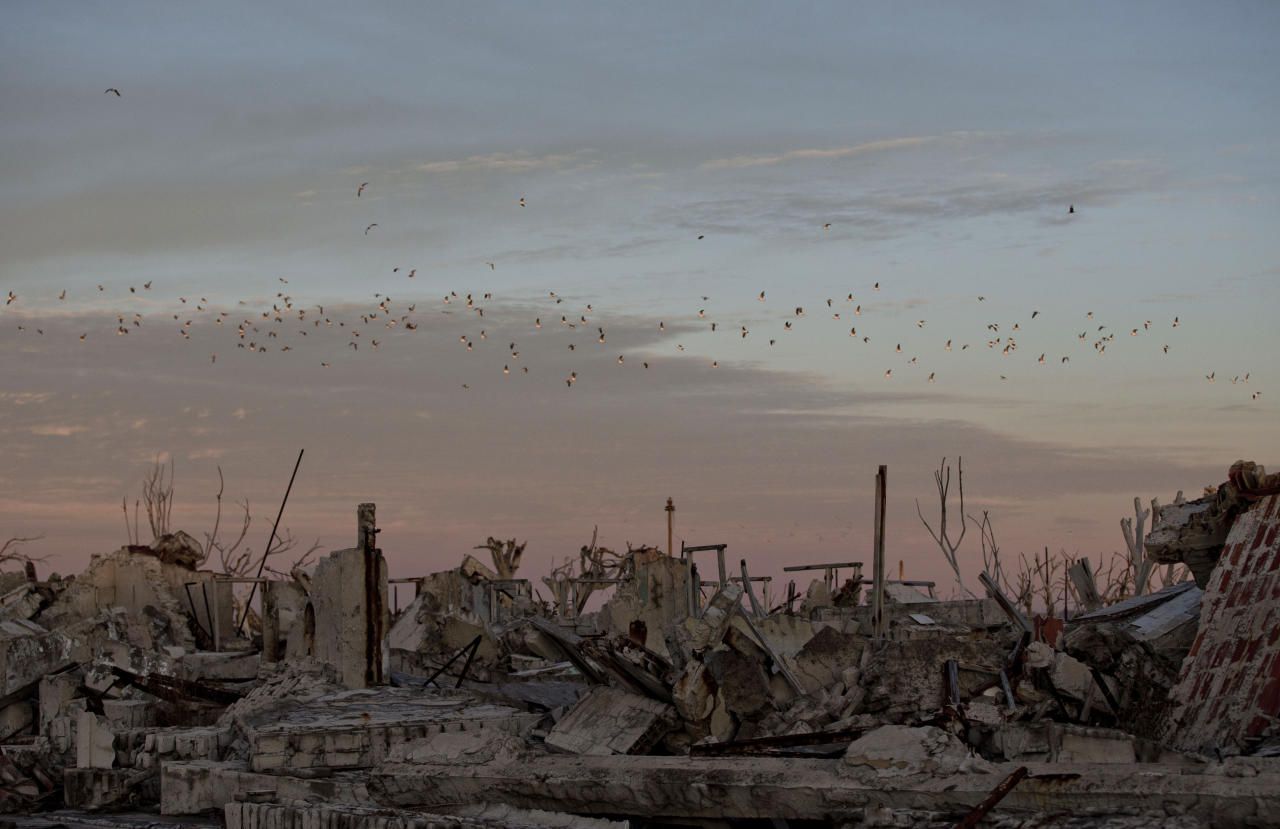 In this May 7, 2013 photo, birds fly over the village of Epecuen, Argentina. Epecuen village was once home to 1,500 residents before it started flooding on November 10, 1985. After heavy rains the lake Epecuen burst its banks . It only took 20 days for the town to submerge beneath almost 10 metres (30 feet) of water forcing everybody to leave. As the years passed slowly the water started to recede. Nowadays the town that was never rebuilt, and was famous for therapeutic salty waters that surrounded it, is once again becoming a tourist destination but for the ruins that have been left. (AP Photo/Natacha Pisarenko)
