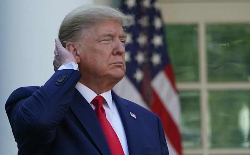 US President Donald Trump pats down his hair as he speaks during the Coronavirus Task Force daily briefing on COVID-19 in the Rose Garden of the White House in Washington, DC on March 30, 2020. (Photo by MANDEL NGAN / AFP) (Photo by MANDEL NGAN/AFP via Getty Images)