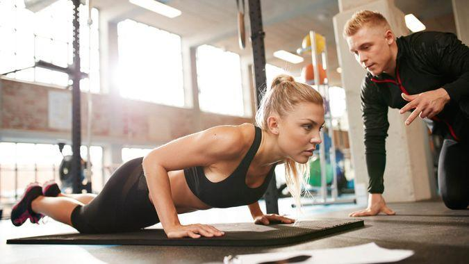 trainer with woman exercising