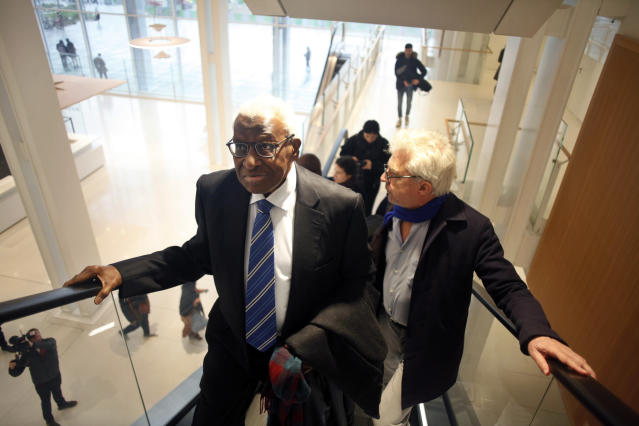 CAPTION CORRECTS SPELLING OF SURNAME Former president of the IAAF (International Association of Athletics Federations) Lamine Diack, left, arrives with his lawyer William Bourdon, right, at the Paris courthouse, Monday, Jan. 13, 2020. One of the biggest sports corruption cases to reach court is being heard in Paris from Monday, with explosive allegations of a massive doping cover-up at the top of track and field. (AP Photo/Thibault Camus)