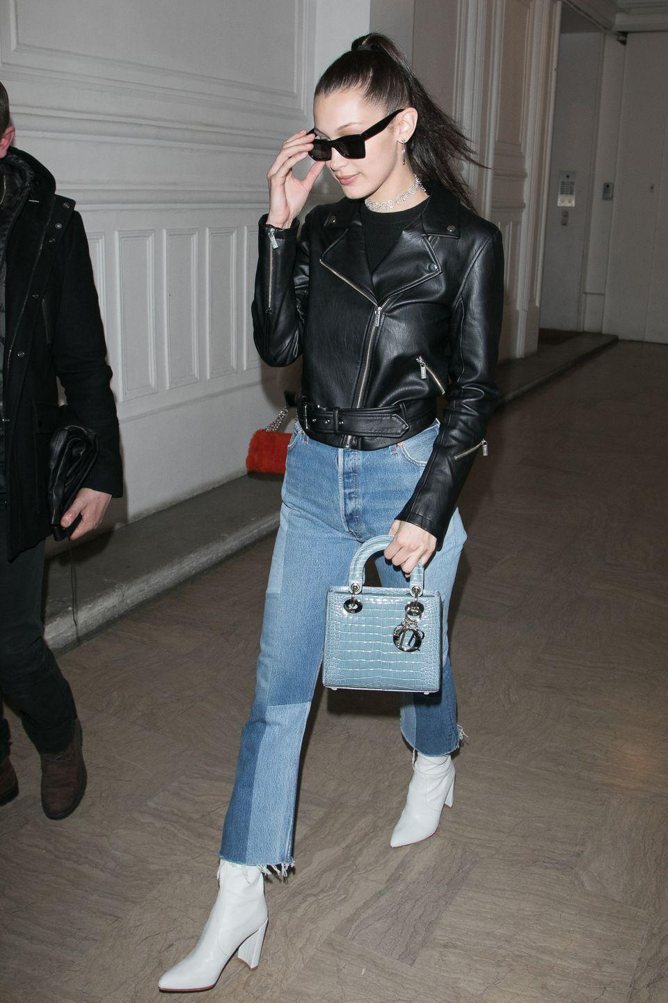 <p>In patched Re/Done jeans, Stuart Weitzman white boots, a baby blue Dior handbag, leather jacket, jeweled choker, silver hoop earrings and Céline sunglasses while out in Paris.</p>