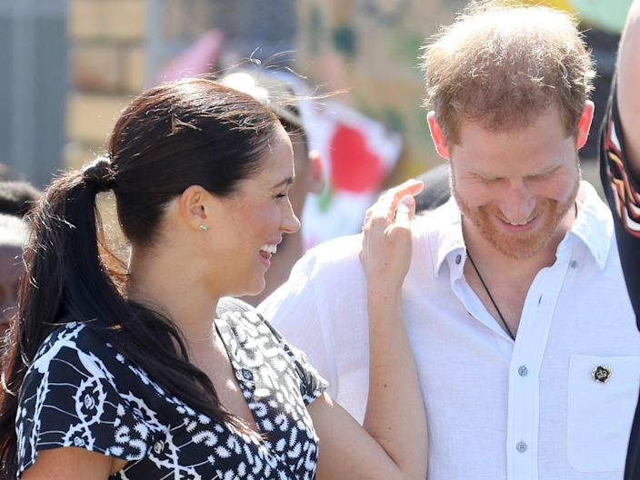 Meghan Markle puts her hand on Prince Harry's shoulder in Cape Town, South Africa.