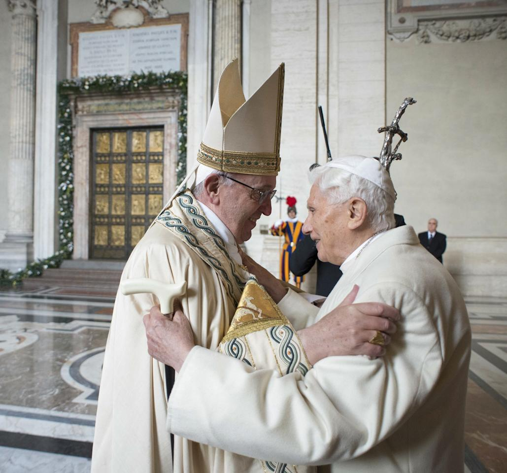 Pope Francis (L) embraces Emeritus Pope Benedict XVI before opening the Holy Door to mark opening of the Catholic Holy Year, or Jubilee, in St. Peter's Basilica, at the Vatican, December 8, 2015. REUTERS/Osservatore Romano/Handout via Reuters ATTENTION EDITORS - THIS IMAGE WAS PROVIDED BY A THIRD PARTY. REUTERS IS UNABLE TO INDEPENDENTLY VERIFY THE AUTHENTICITY, CONTENT, LOCATION OR DATE OF THIS IMAGE. IT IS DISTRIBUTED EXACTLY AS RECEIVED BY REUTERS, AS A SERVICE TO CLIENTS. FOR EDITORIAL USE ONLY. NOT FOR SALE FOR MARKETING OR ADVERTISING CAMPAIGNS. NO RESALES. NO ARCHIVE.      TPX IMAGES OF THE DAY