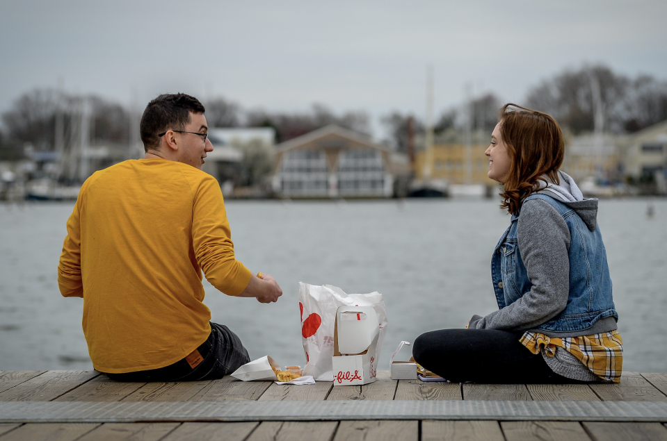 Cameron Shaver and Callie Johnson practice social distancing to prevent the spread of coronavirus disease (COVID-19) as they enjoy dinner at City Dock in Annapolis, U.S., March 18, 2020. (Photo: REUTERS/Mary F. Calvert)