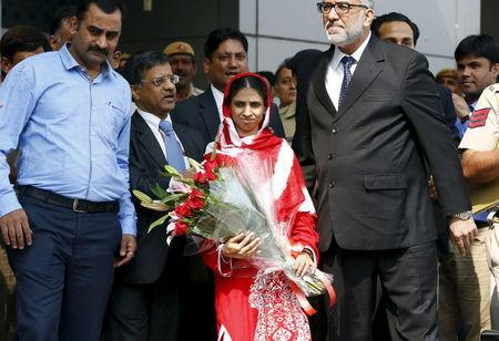 Geeta holds a bouquet of flowers as she comes out from an airport after her arrival in New Delhi, India, October 26, 2015. REUTERS/Adnan Abidi