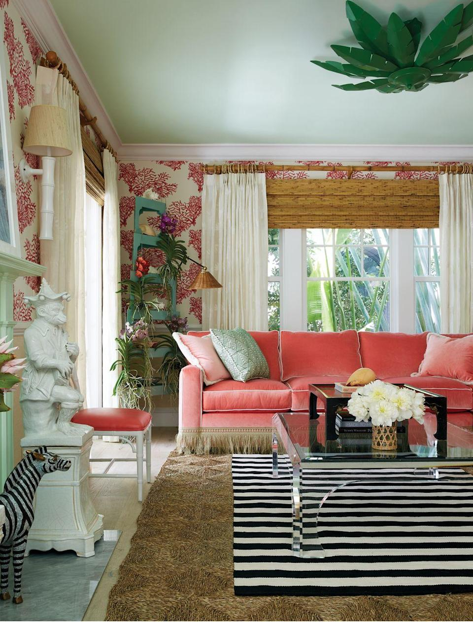 """<p>Defined by its extroverted yet cultivated qualities, preppy rooms are """"steadfast arenas for the tumble of life,"""" according to Caponigro. Those drawn to the upbeat mode will most certainly love juicy pink and coral tones like those featured on the velvet sofa (Sophia Velvet) and playful wallcovering (Great Barrier Reef) in this Amanda Lindroth–designed living room. </p>"""