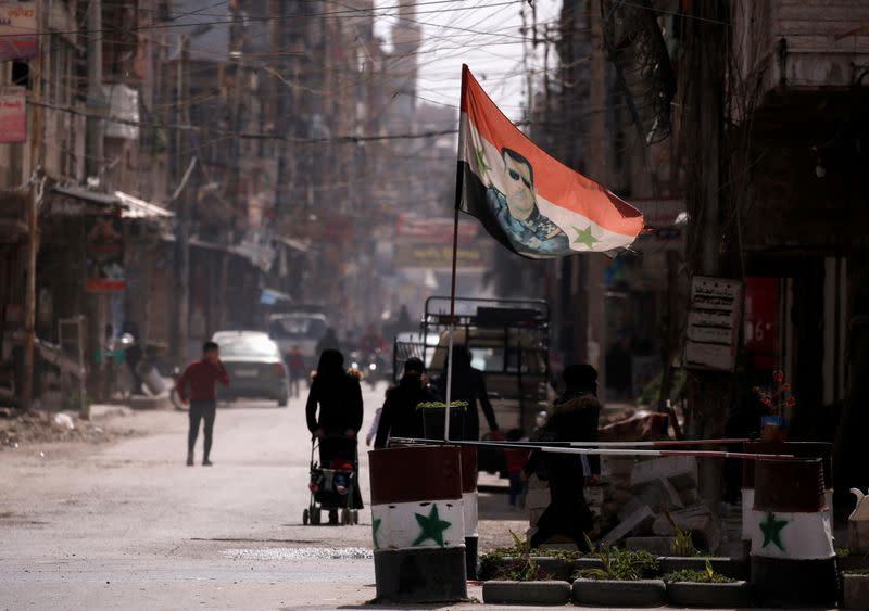 FILE PHOTO: A national flag depicting a picture of Syria's President Bashar al-Assad flutters at a checkpoint in Douma