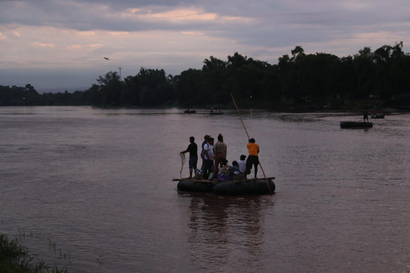 Migrants travel from Guatemala to Mexico on a raft, pushed with a pole by its operator who charges his passengers, across the Suchiate River near Ciudad Hidalgo, Mexico, early Sunday, June 9, 2019. Mexican and U.S. officials reached an accord late Friday that calls on Mexico to crackdown on migrants in exchange for Trump backing off his threat to impose a 5% tariff on Mexico's exports if it did not stem the flow of Central American migrants crossing its territory toward the U.S. (AP Photo/Marco Ugarte)