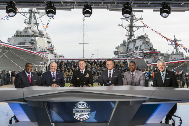 """In this 2017 photo provided by Fox Sports, from left to right, Curt Menefee, Terry Bradshaw, Adm. Phil Davidson, commander of U.S. Fleet Forces, Howie Long, Michael Strahan and Jimmy Johnson pose during the """"Fox NFL Sunday"""" pregame show at Naval Station-Norfolk. This year's Salute to Veterans Day show will originate from the U.S. Military Academy at West Point. (Jen Pransky/Fox Sports via AP)"""