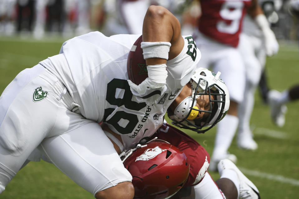 Portland State tight end Charlie Taumoepeau is taken down by an Arkansas defender in the first half of an NCAA college football game, Saturday, Aug. 31, 2019 in Fayetteville, Ark. (AP Photo/Michael Woods)