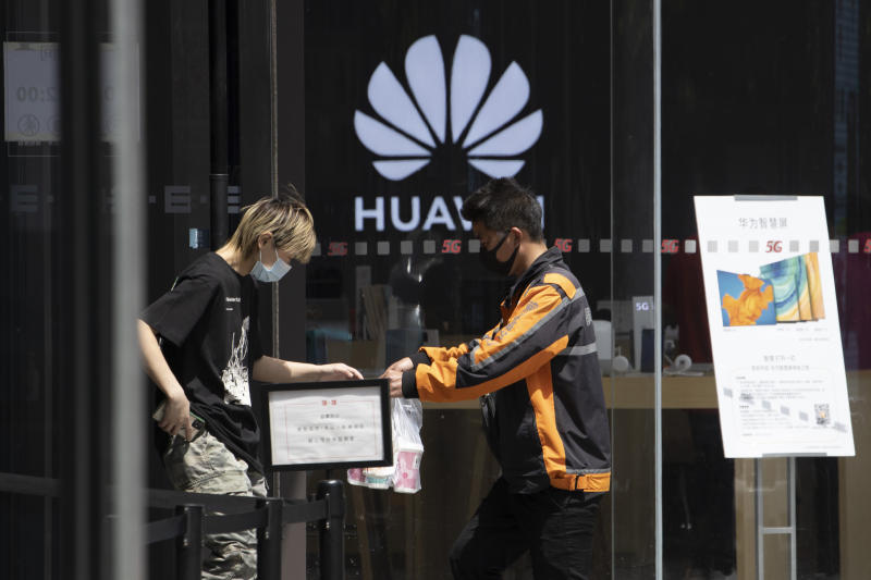 """A delivery man hands over drinks near a Huawei retail store in Beijing on Monday, May 18, 2020. China's commerce ministry says it will take """"all necessary measures"""" in response to new U.S. restrictions on Chinese tech giant Huawei's ability to use American technology, calling the measures an abuse of state power and a violation of market principles. (AP Photo/Ng Han Guan)"""