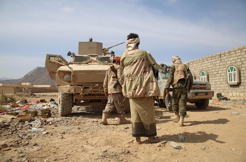 Armed Yemeni tribesmen from the Popular Resistance Committees, supporting forces loyal to Yemen's Saudi-backed President Abedrabbo Mansour Hadi, stand next to armoured vehicles west of Marib city