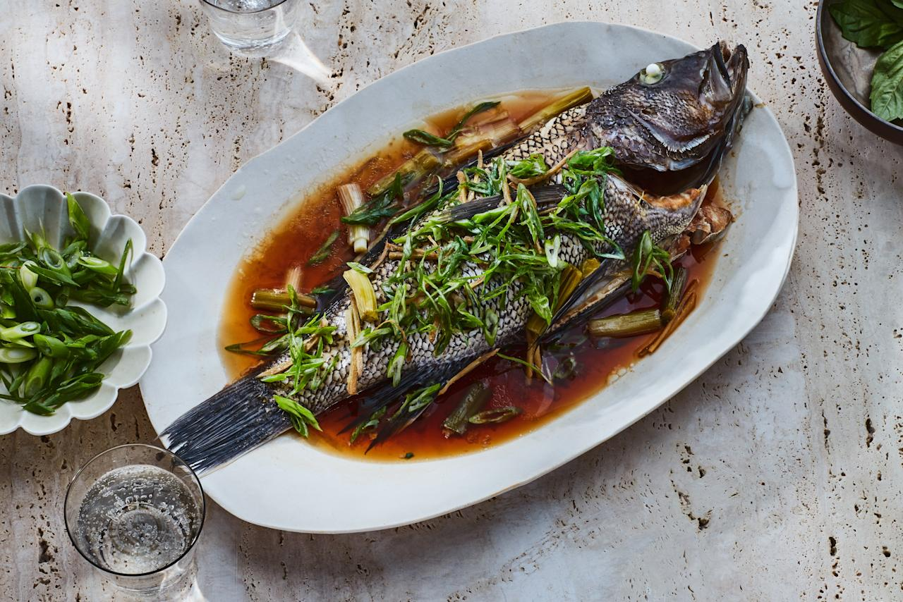 """A whole fish, representing abundance, is almost always included on the celebratory Lunar New Year. Ours is flavored only lightly, with ginger and scallions, so as not to overpower the fresh taste of the fish. We developed an oven-steaming method to free up space on your stovetop for soup, dumplings, and stir-fries. <a href=""""https://www.epicurious.com/recipes/food/views/whole-black-bass-with-ginger-and-scallions-233789?mbid=synd_yahoo_rss"""">See recipe.</a>"""