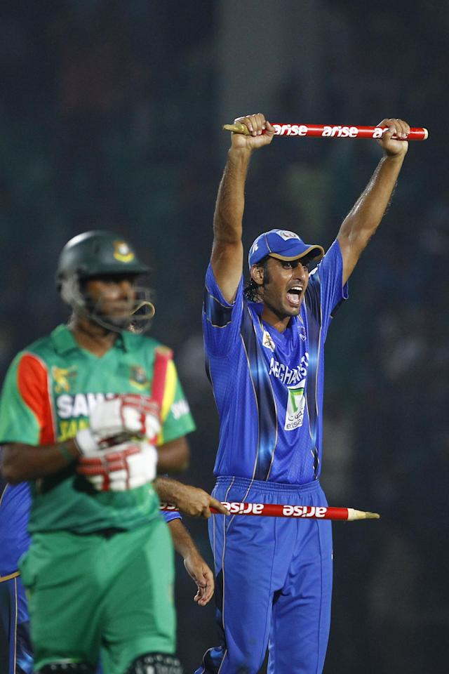 Afghanistan's Shapoor Zadran, right, celebrates with a stump after winning the Asia Cup one-day international cricket tournament against Bangladesh in Fatullah, near Dhaka, Bangladesh, Saturday, March 1, 2014. (AP Photo/A.M. Ahad)