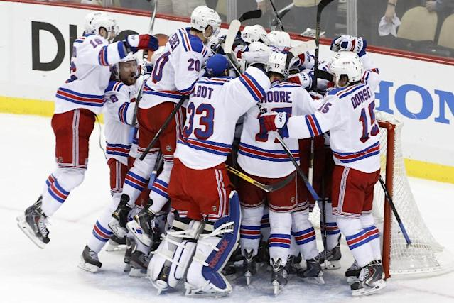New York Rangers goalie Henrik Lundqvist is swarmed by teammates Game 7 of a second-round NHL playoff hockey series against the Pittsburgh Penguins in Pittsburgh Tuesday, May 13, 2014. The Rangers won 2-1 and advanced to the conference finals. (AP Photo)