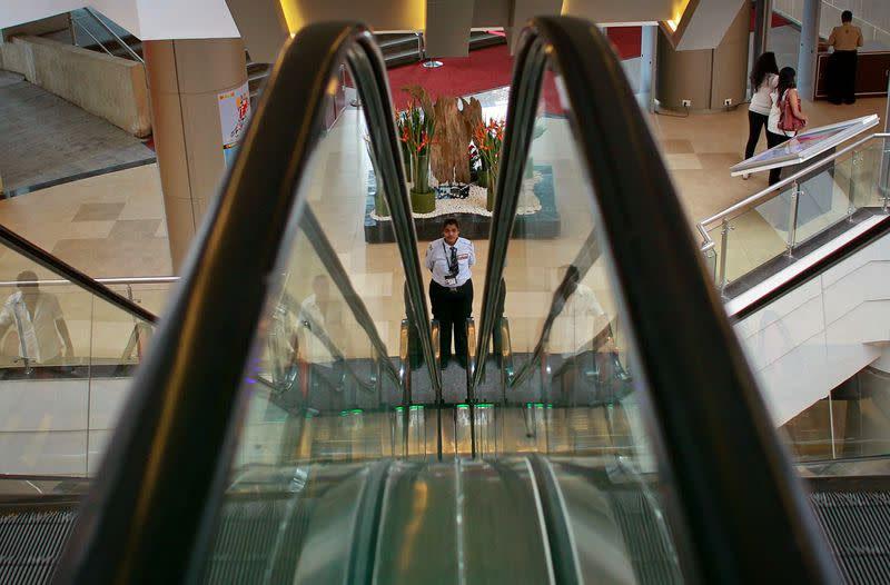 A security guard stands between escalators inside a shopping mall in Mumbai