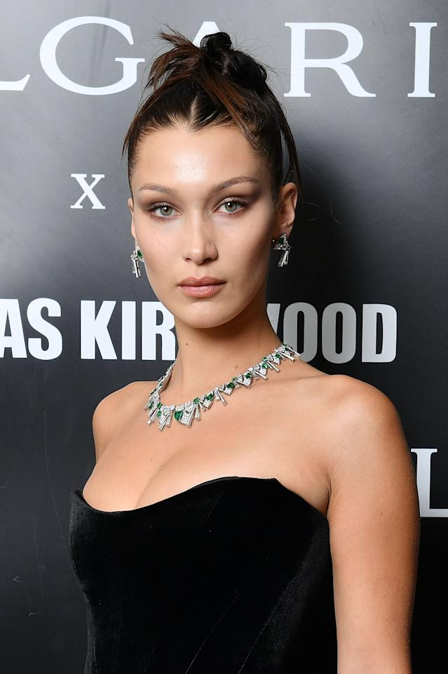 <p>While attending an event in 2017, Hadid wore this tight top knot with the ends sticking out toward her face. </p>