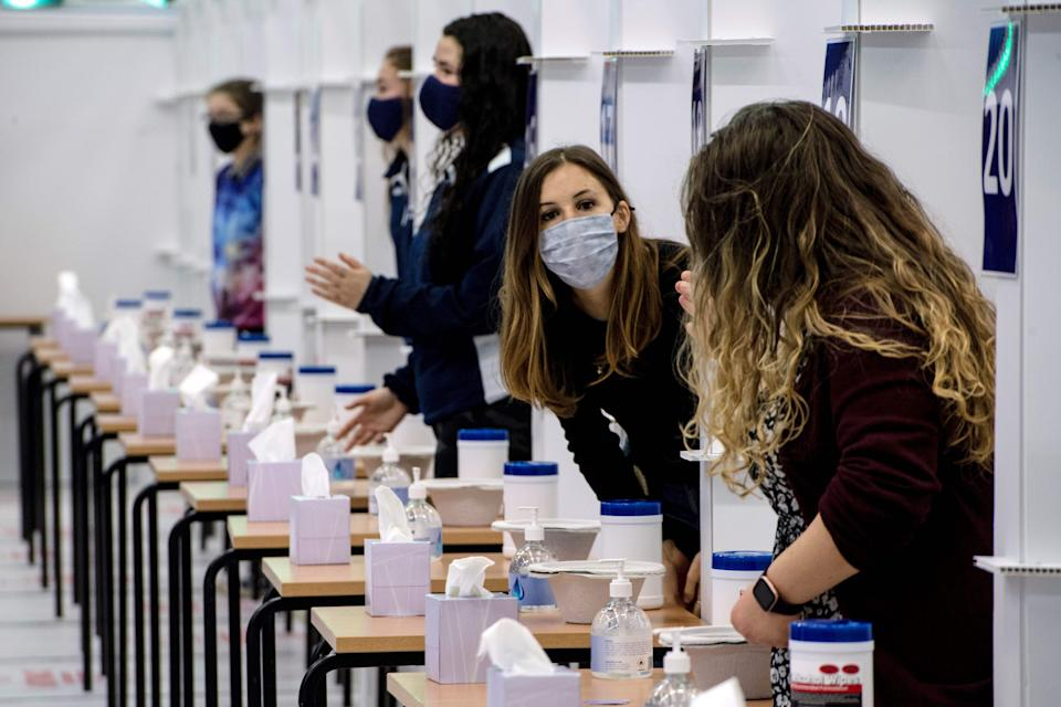 Students from the University of St. Andrews wait to take a lateral-flow test in a mass COVID-19 testing centre, set up in the University's sports hall in St. Andrews, eastern Scotland on November 27, 2020, to determine if they are able to travel home for the Christmas break. (Photo by Andy Buchanan / AFP) (Photo by ANDY BUCHANAN/AFP via Getty Images)