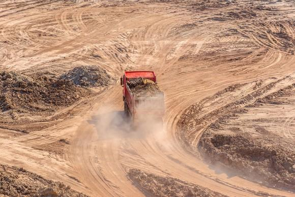 A mining truck driving on a dusty road.