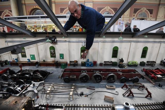 A model engineer looks at pieces from a model train depot
