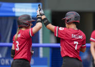 Canada's Jenn Salling, right, is congratulated by teammate Erika Polidori after hitting a home run during the softball game between Mexico and Canada at the 2020 Summer Olympics, Wednesday, July 21, 2021, in Fukushima , Japan. (AP Photo/Jae C. Hong)