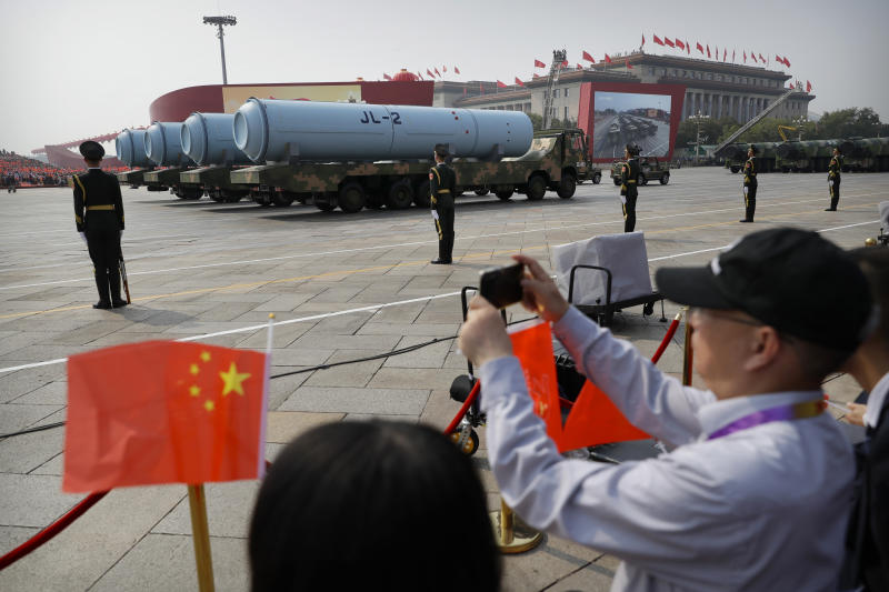 FILE - In this Oct. 1, 2019, file photo, spectators wave Chinese flags as military vehicles carrying JL-2 submarine-launched missiles roll during a parade to commemorate the 70th anniversary of the founding of Communist China in Beijing. China will boost defense spending by just 6.6% in 2020, the lowest rate in years as it battles an economic crisis brought on by the coronavirus outbreak, the government said Friday, May 22, 2020. (AP Photo/Mark Schiefelbein, File)