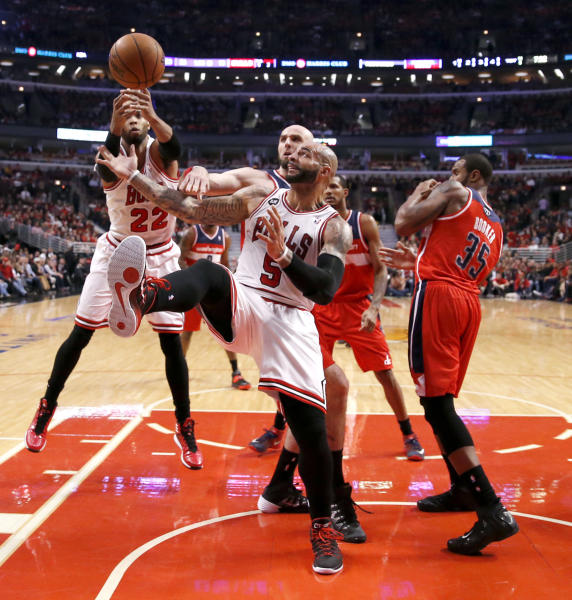 Chicago Bulls forward Taj Gibson (22) and forward Carlos Boozer (5) battle Washington Wizards center Marcin Gortat for a rebound as Trevor Booker (35) stands enar during the first half of Game 5 in an opening-round NBA basketball playoff series Tuesday, April 29, 2014, in Chicago. (AP Photo/Charles Rex Arbogast)