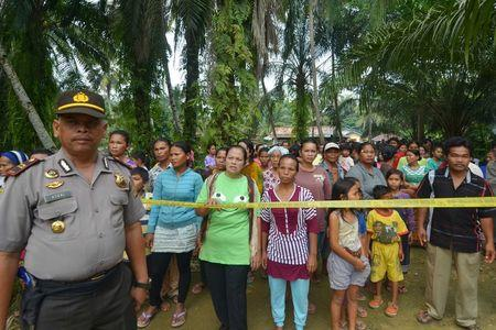 Residents look on as a policeman stands guard in Suka Makmur village in Singkil district, Indonesia Aceh province