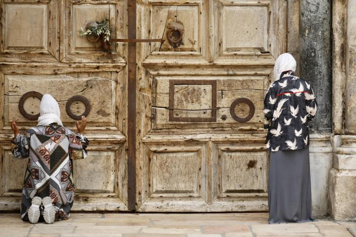 Women pray iin front of the closed Church of the Holy Sepulchre, a place where Christians believe Jesus Christ was buried, as a palm hangs on the door, in Jerusalem's Old City, Sunday, April 5, 2020. The traditional Palm Sunday procession was cancelled due to restrictions imposed to contain the spread of the coronavirus. (AP Photo/Ariel Schalit)