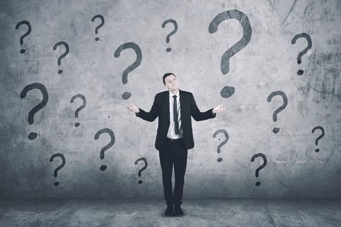 Businessman shrugging and holding hands out with question marks on the wall behind him