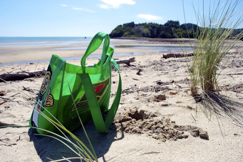 Takaka, New Zealand - October 07th 2014. A Four Square Green Carrier Bag from the Retailer Chain 4 Square Supermarket at the Liger Bay Beach, Golden Bay, Tasman Region of the South Island of New Zealand.