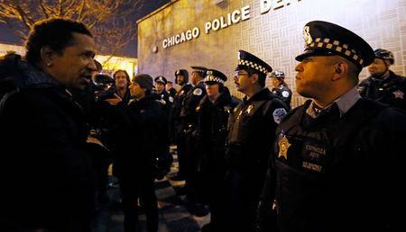 A demonstrator faces a line of police in front of the Chicago Police Department during protests in Chicago, November 24, 2015. REUTERS/Jim Young