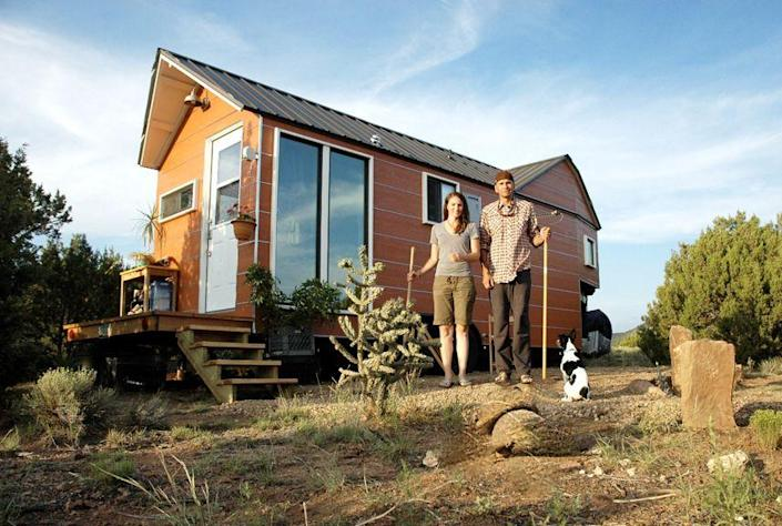 """<p>Carrie and Shane Caverly built their 200-square-foot house in the spring of 2012 after growing tired of paying mortgages and rent. Built on a trailer, the house features a low-maintenance steel roof, an on-demand hot water heater, an incinerating toilet, and a passive solar design. Carrie, an architectural designer, and Shane, a custom builder, now run <a href=""""http://clotheslinetinyhomes.com/shop/"""" rel=""""nofollow noopener"""" target=""""_blank"""" data-ylk=""""slk:Clothesline Tiny Homes"""" class=""""link rapid-noclick-resp"""">Clothesline Tiny Homes</a>, offering downloadable tiny house plans, design consulting, and custom building. After living in their tiny house for 20 months in New Mexico, the couple has now moved to Colorado, where they're building a 1,000-square-foot home. (Their tiny house will serve as a guest cottage.) </p><p><a class=""""link rapid-noclick-resp"""" href=""""http://clotheslinetinyhomes.com/house-photos/"""" rel=""""nofollow noopener"""" target=""""_blank"""" data-ylk=""""slk:SEE INSIDE"""">SEE INSIDE</a></p>"""